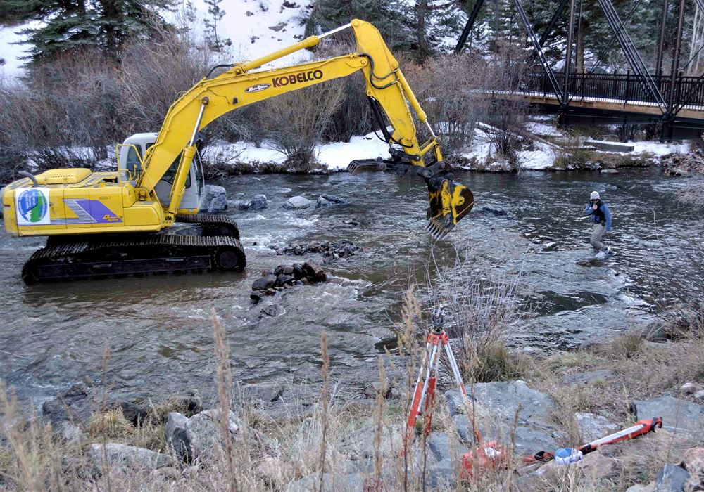 A backhoe digging into a river